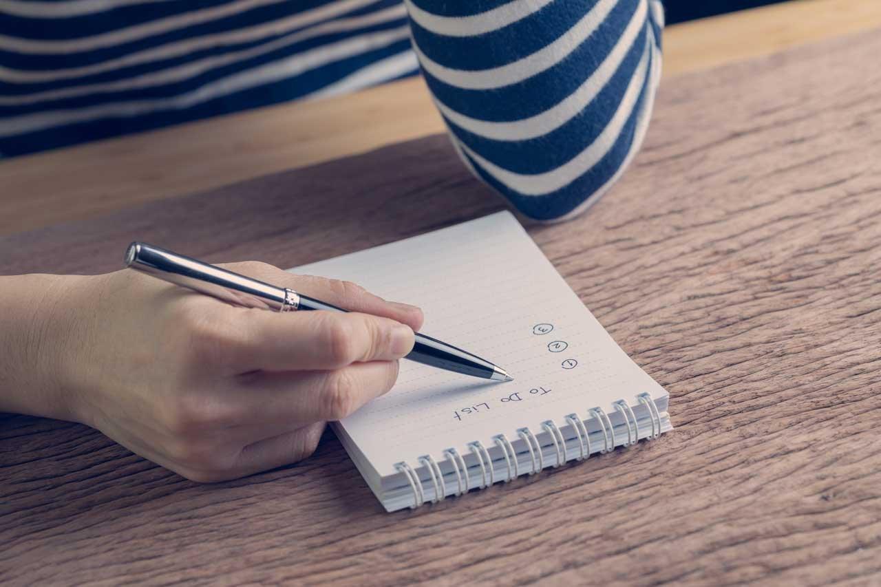 Person schreibt eine Prioritätenliste zur Burnout-Prävention