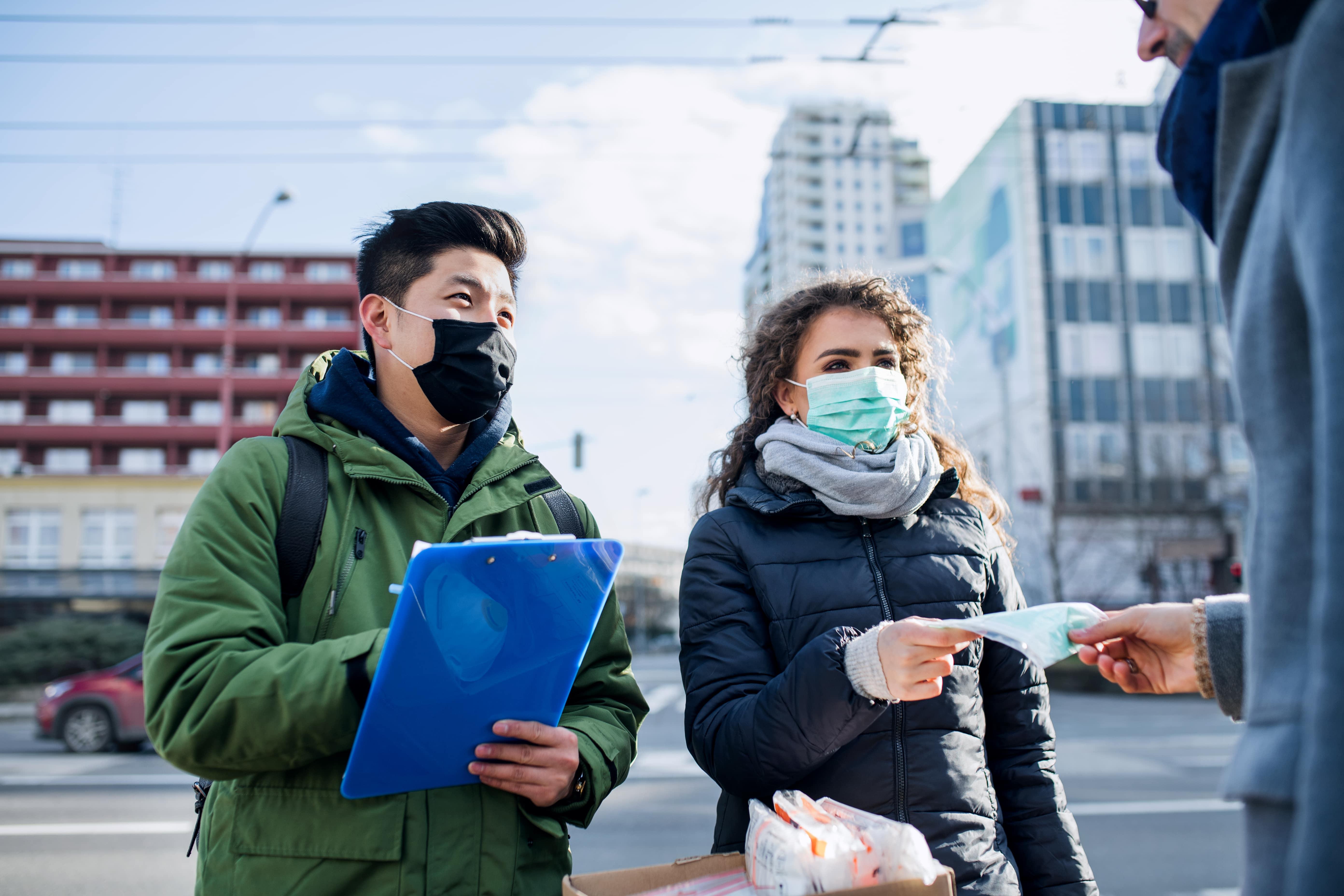 Passanten tragen eine Mund-Nasen-Bedeckung zur Prävention einer Corona-Infektion im öffentlichen Raum