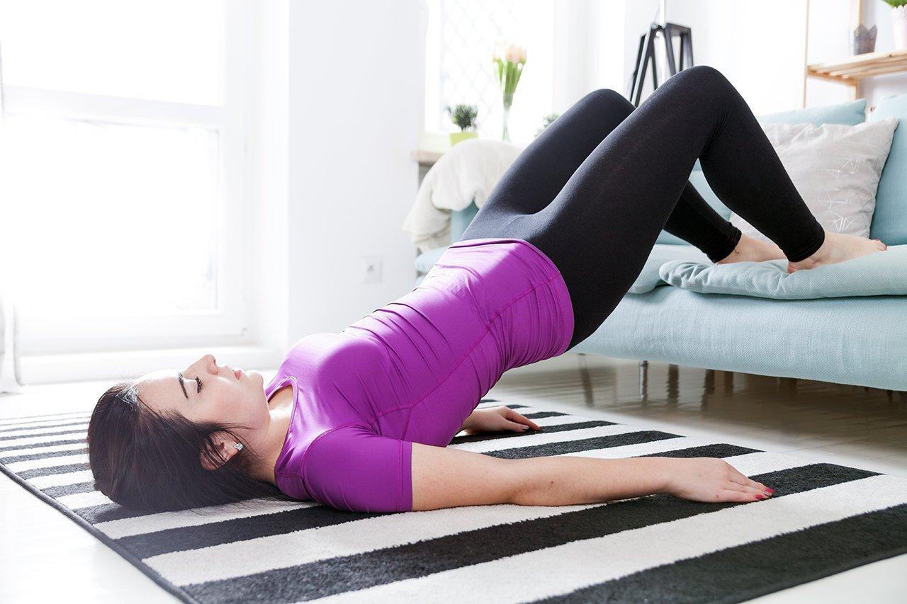 Die Rückenübung für zuhause wird mit einer Erhöhung für die Füße ausgeführt.