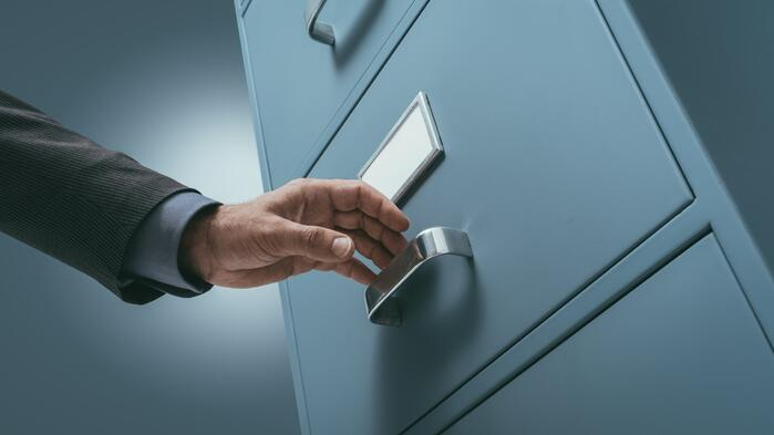 office-clerk-searching-files-in-the-filing-cabinet-P9J56MW-min