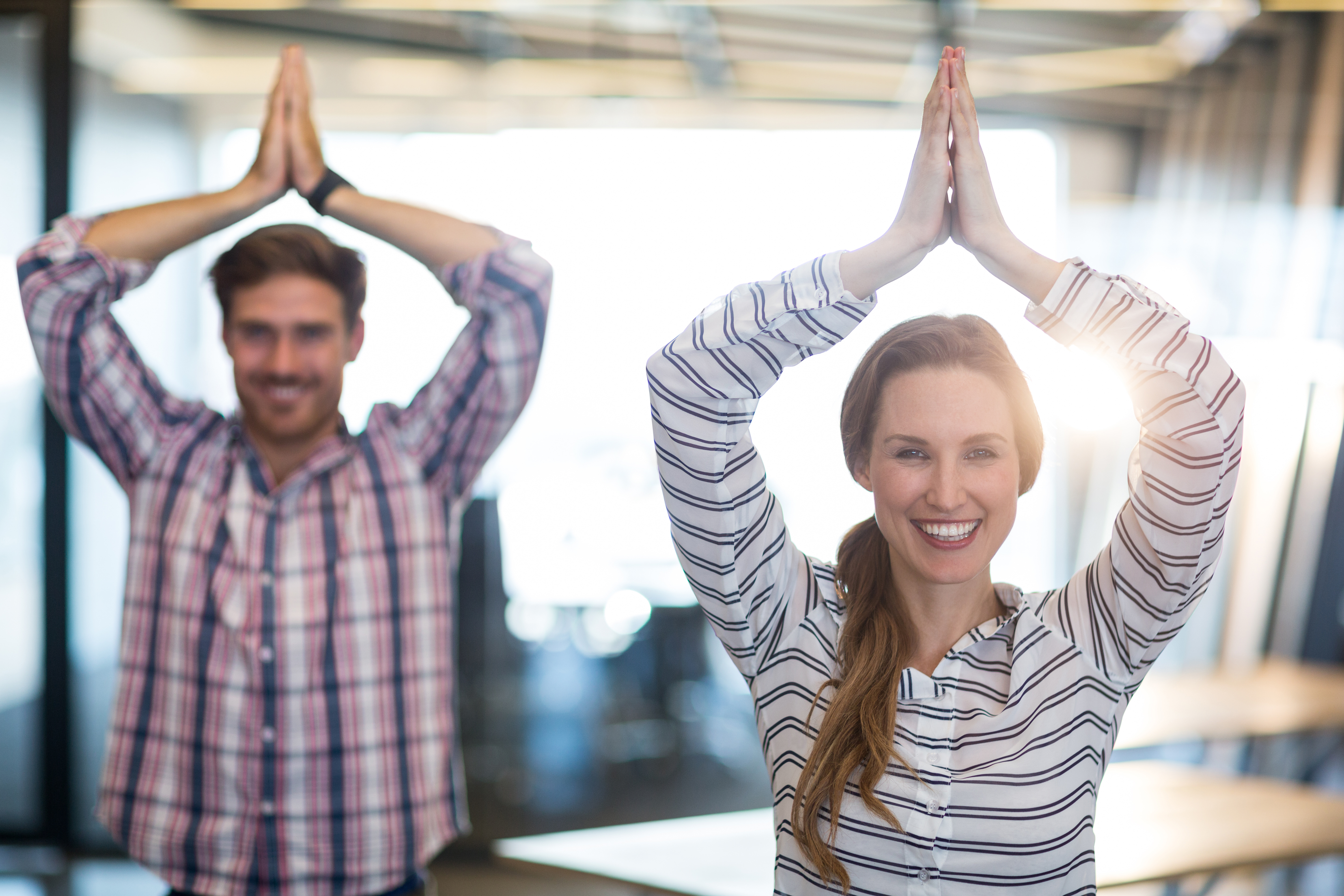 smiling-business-people-performing-yoga-in-office-X6QVVD9