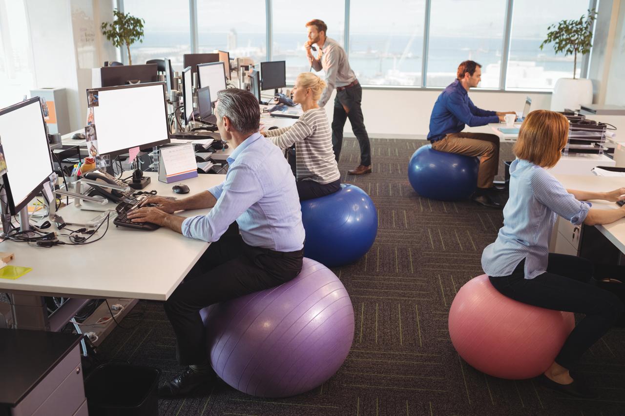 Mitarbeiter sitzen auf Gymnastikbällen.