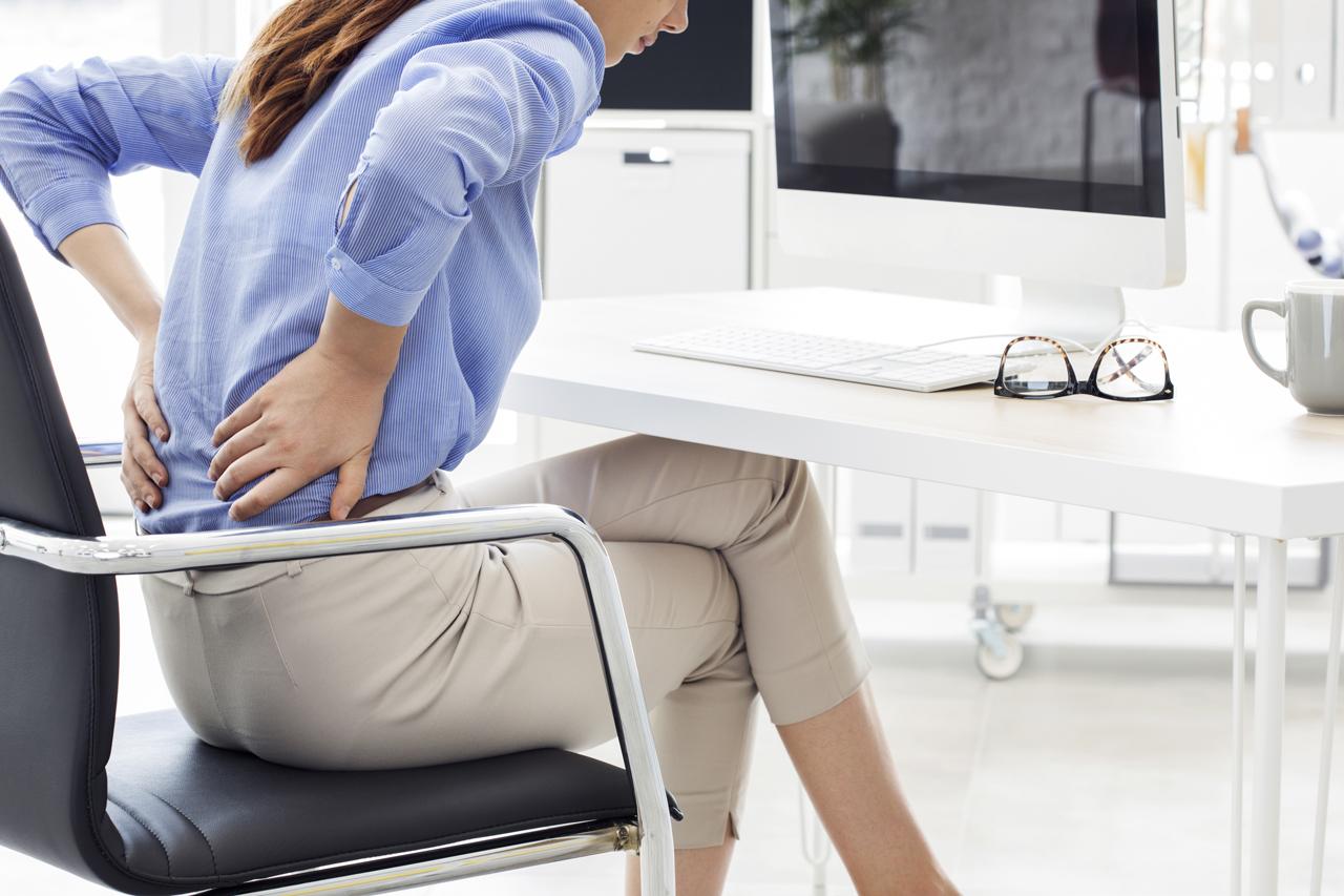 Frau im Büro mit Schmerzen beim Sitzen