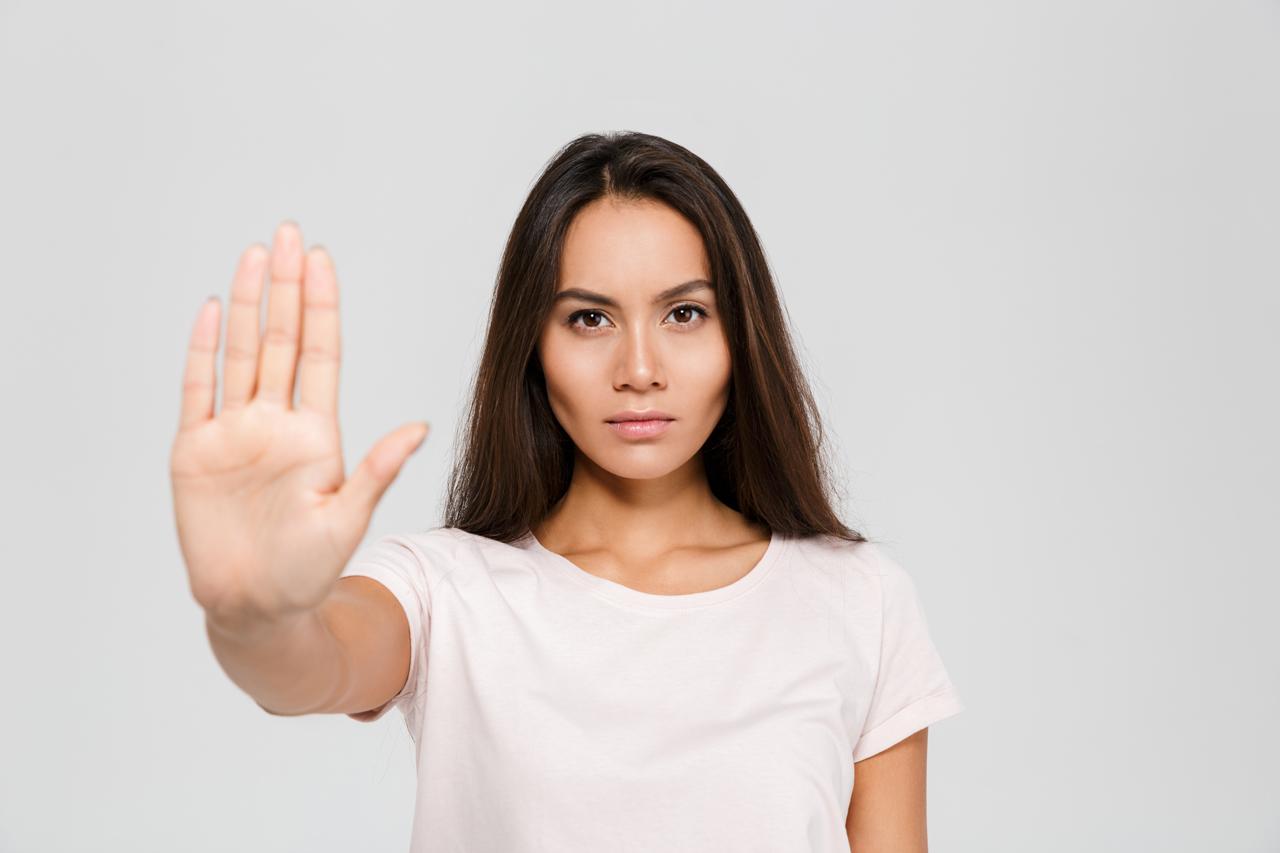 Frau mit ausgestreckter Hand als Zeichen zum Vermeiden von Stress
