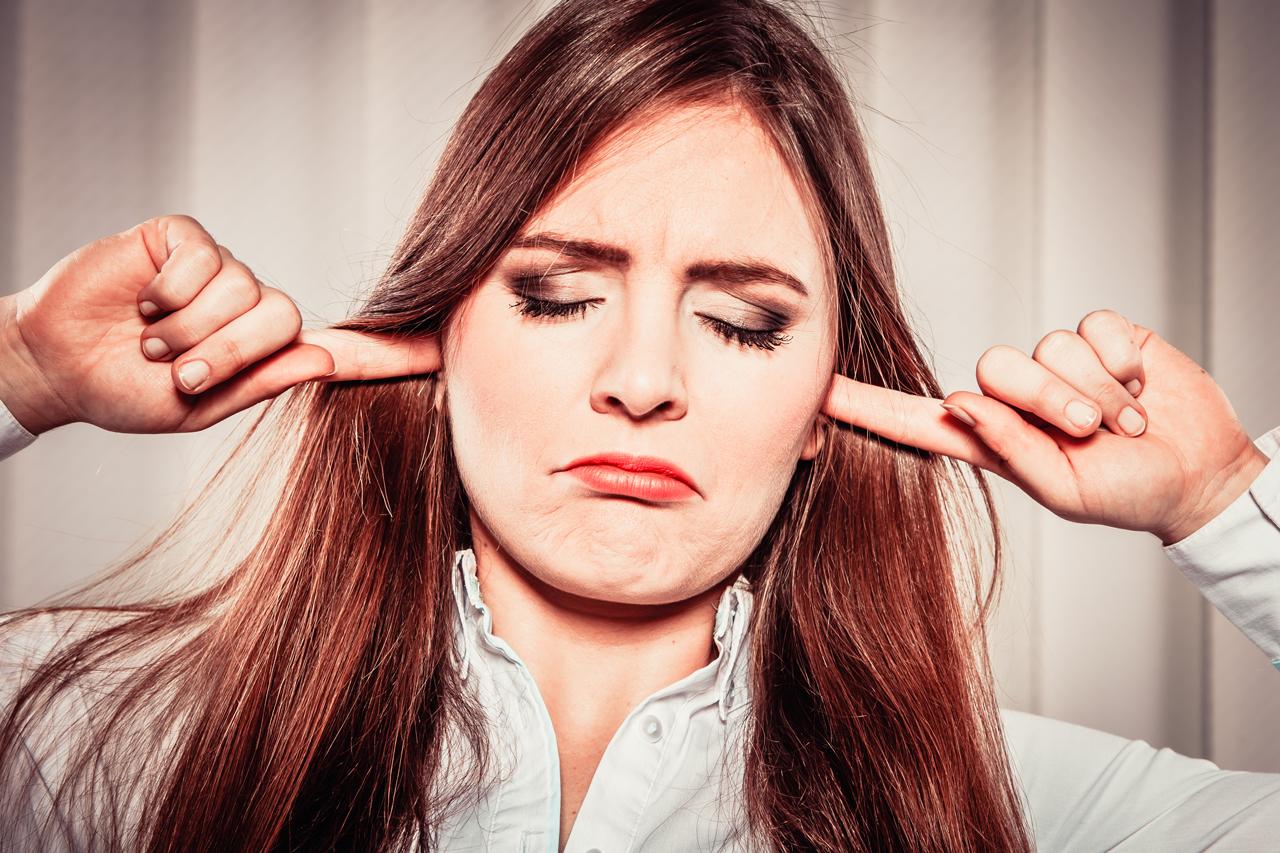 Frau mit zugehaltenen Ohren als Zeichen zum Vermeiden von Stress