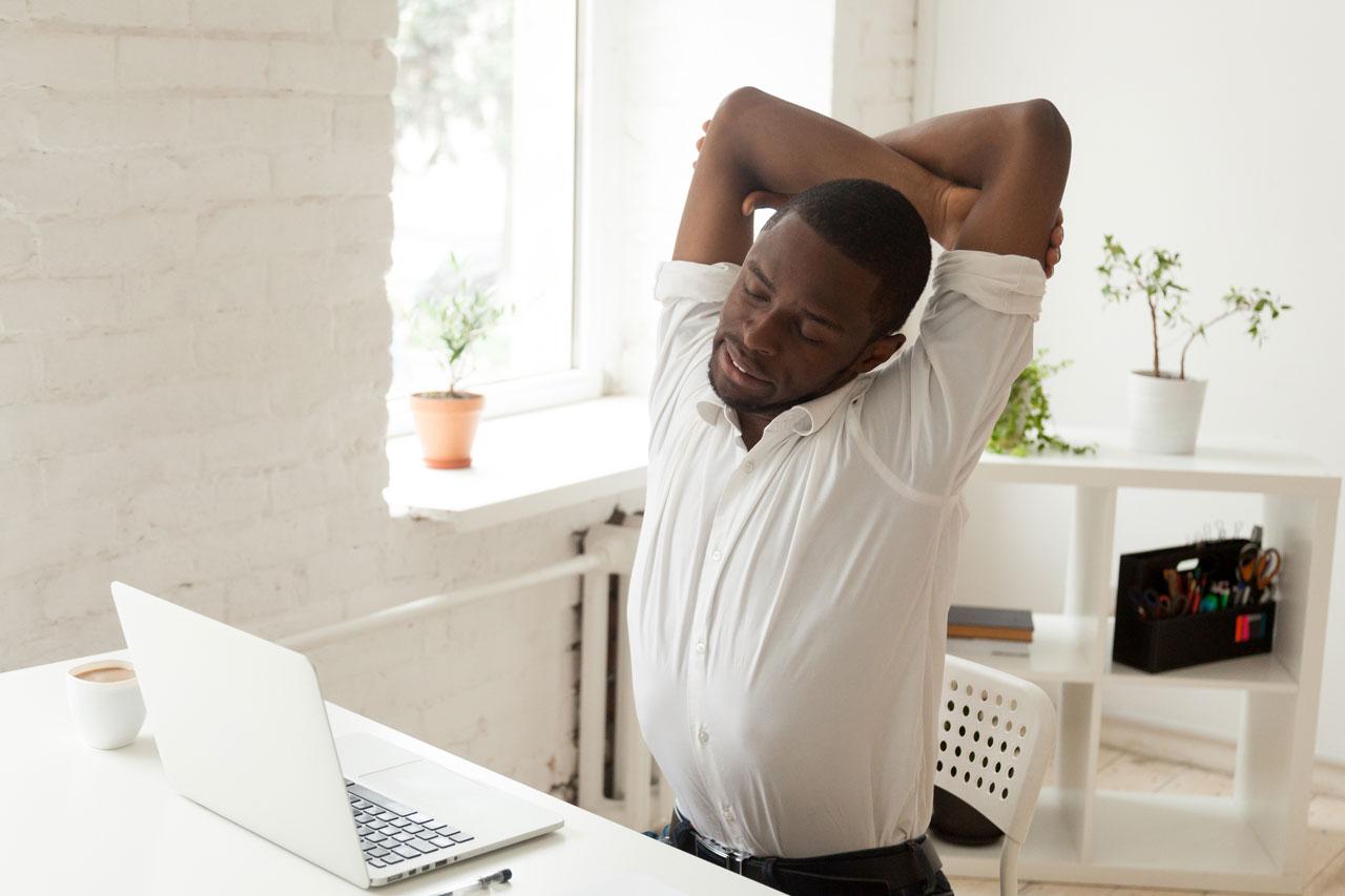Richtiges Sitzen im Büro ist wichtig für unsere Gesundheit. Sich regelmäßig zu bewegen und strecken gehört auch dazu.