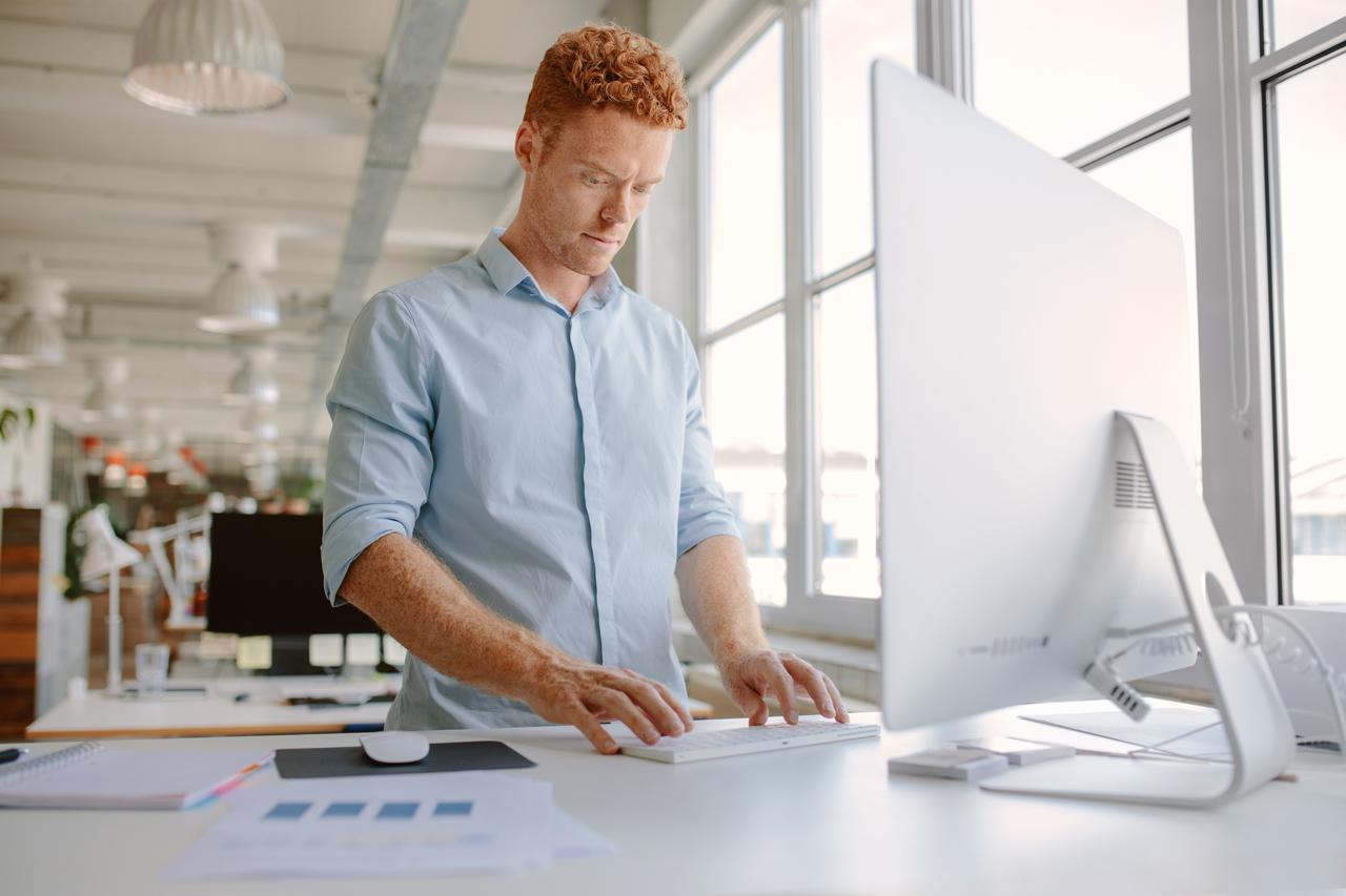 Mann steht am Schreibtisch wegen Schmerzen beim Sitzen