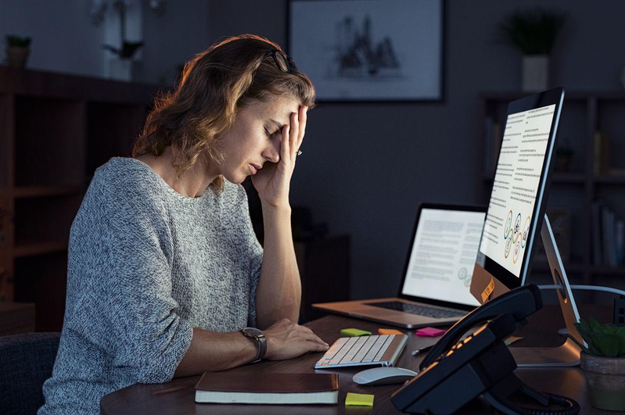 Frau sitzt erschöpft vor ihrem Laptop, und leidet unter einer Depression.
