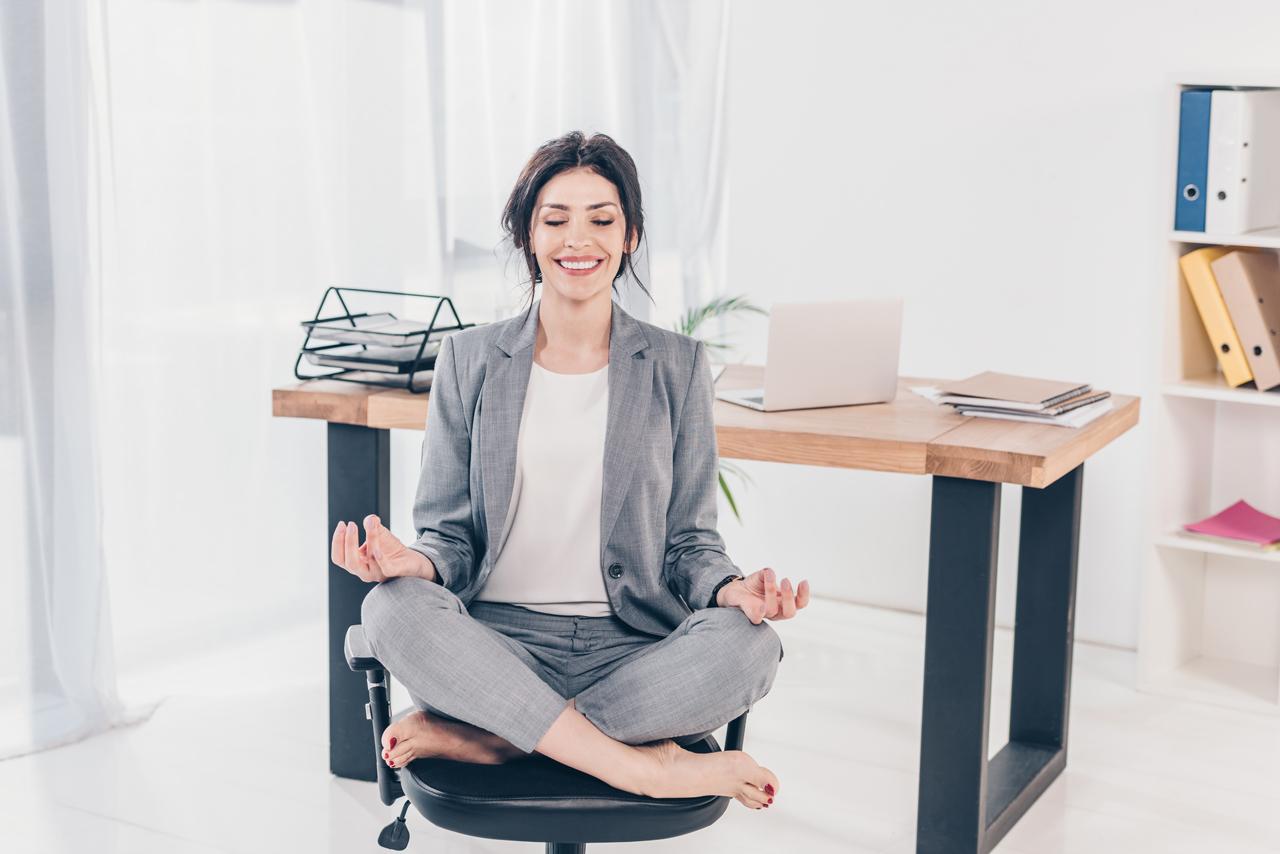 Frau im Schneidersitz auf dem Bürostuhl zum richtig sitzen