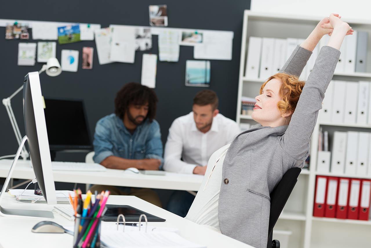 Frau streckt sich für Sport im Büro
