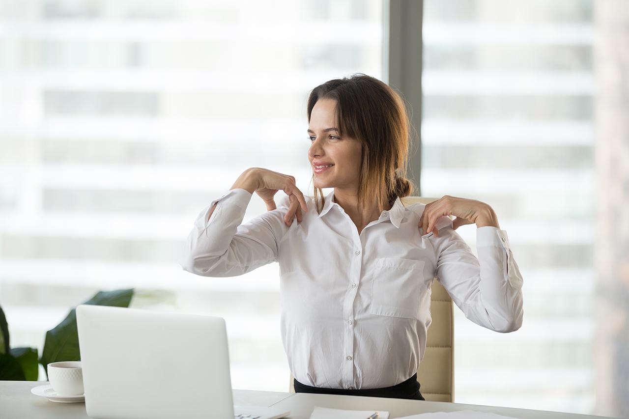 Frau macht Schulterübung für Sport im Büro